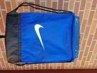 GYMSACK ROYAL WITH BLACK BOTTOM AND DRAWSTRINGS, WHITE SWOOSH ON FRONT, JUST DO IT TONAL DOWN RIGHT BACK, ZIPPER LEFT BACK